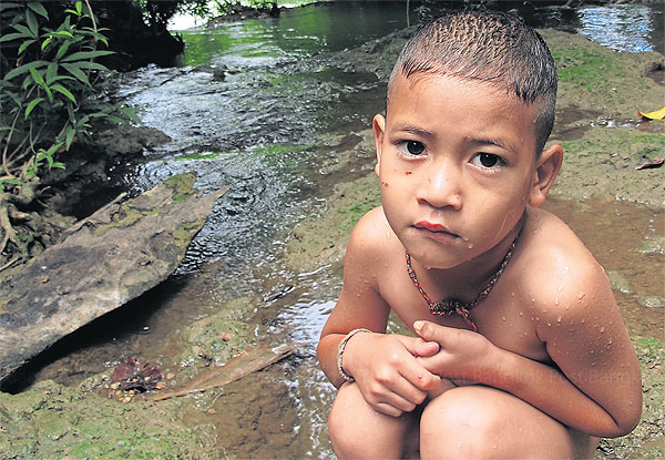 A boy takes a rest after swimming in the lead-laden Klity Creek in a national forest in Kanchanaburi province. Despite a court order two years ago, the Pollution Control Department has not started cleaning up the creek.Intarachai Panitchakul