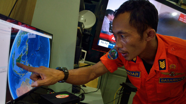 An official from Indonesia's national search and rescue agency in Medan, North Sumatra points at his computer screen to the position where AirAsia flight QZ8501 went missing off the waters of Indonesia