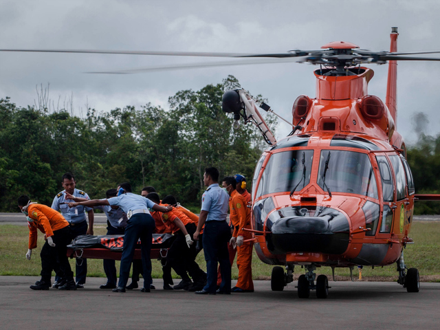 Members of Indonesian search and rescue team carry the body of a passenger of AirAsia flight QZ 8501
