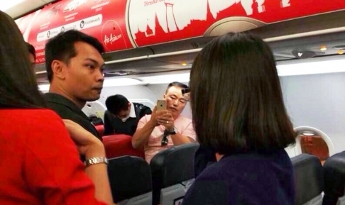 An angry passenger glares along the plane, while another records the incident on his mobile phone