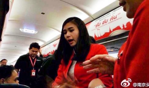A Thai stewardess attempts to ease tensions in the aircraft