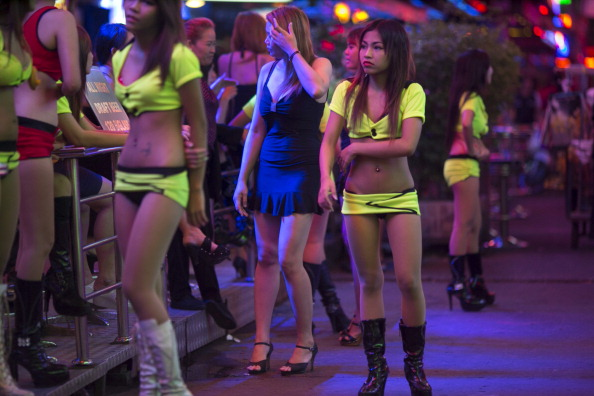 A woman waits for business in the red light district called ' Soi Cowboy' as sex tourism continues