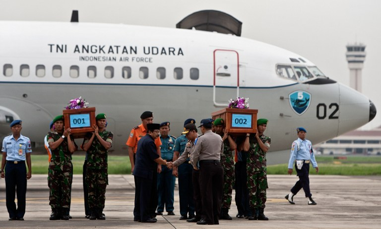 Indonesian military personnel carry the coffin of a victim recovered from the ill-fated Malaysian air carrier AirAsia flight QZ8501 upon their arrival at the military airbase in Surabaya