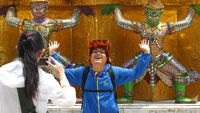 A Chinese tourist strikes a similar pose to statues as they visit the Grand Palace in Bangkok