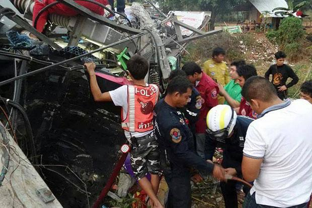 Police examine the wreckage of the tour bus after it crashed into a roadside power pole and overturned in Wang Thong district of Phitsanulok Please credit and share this article with others using this link:http://www.bangkokpost.com/news/general/487616/tour-bus-crash-kills-6-injures-42. View our policies at http://goo.gl/9HgTd and http://goo.gl/ou6Ip. © Post Publishing PCL. All rights reserved.