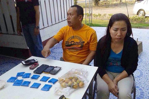 Pol Snr Sgt Maj Sompong Sitthi, 46, of Nam Muab police station in Nan's Wiang Sa district, and his wife Puangpaka, 44, alongside packs of speed pills at a press conference