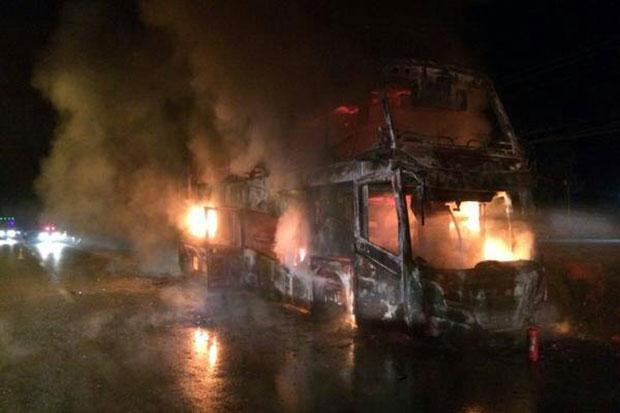 The double-decker tour bus engulfed in flames in Chumphon's Sawi district early Thursday. All 34 foreign tourists on board, and the driver, escaped unhurt. (Photo by Facebook www.js100.com)
