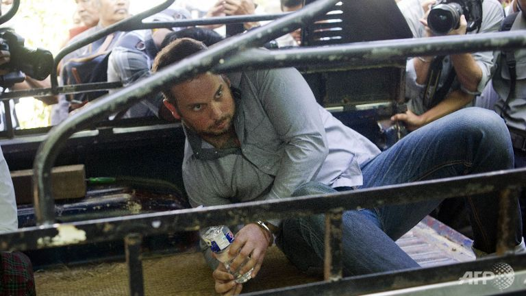 Philip Blackwood (C), a New Zealand bar manager, is pictured in the back of a vehicle surrounded by the media as he attends a court hearing in Yangon