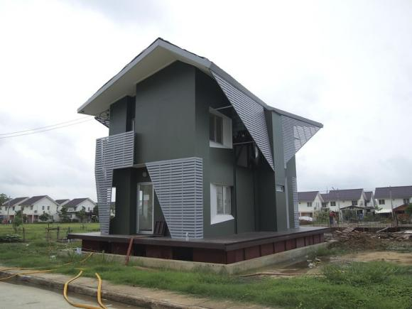 In this picture provided by Site-Specific Co Ltd, the 2.8 million baht ($86,000) amphibious house, designed and built by the architecture firm Site-Specific Co Ltd for Thailand's National Housing Authority (NHA) rises up 85cm after architects and NHA staff fill a manmade test hole underneath the house with water during a trial run in Ban Sang village of Ayutthaya province