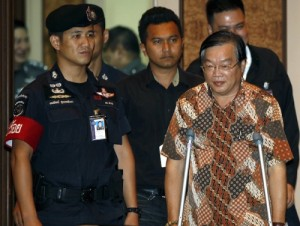Malaysian Teo Boon Ching is escorted by police officers before a news conference in Bangkok