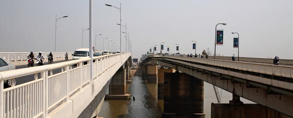 A bridge, right, built with Japan's support and another constructed with China's assistance stand side by side over the Tonle Sap River in Phnom Penh.
