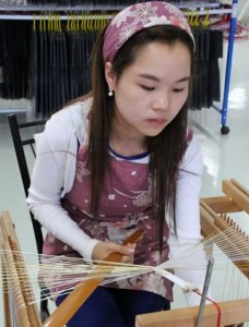 A worker weaves a braided cord for Japanese kimono at Ando's plant in Pakse, Laos