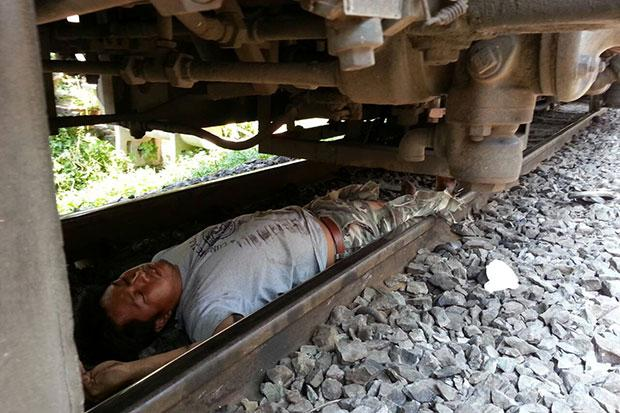 Supakorn Trakulkaew, 35, is found lying on the tracks with minor bruises after jumping in front of a train in Nakhon Sawan around noon on April 3. (Photo by Chalit Pumruang)