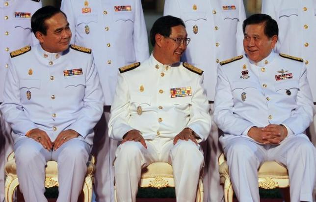 (L-R) Thailand's Prime Minister Prayuth Chan-ocha and Deputy Prime Minister Pridiyathorn Devakula speak with Deputy Prime Minister and Foreign Minister General Tanasak Patimapragorn during a photo session at the Government House in Bangkok