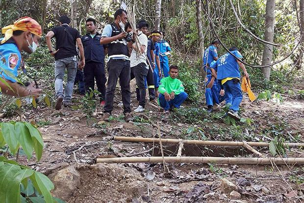 Rescue workers and forensic officials inspect the site of a mass grave uncovered at an abandoned jungle camp in the Sadao district of Songkhla province bordering Malaysia