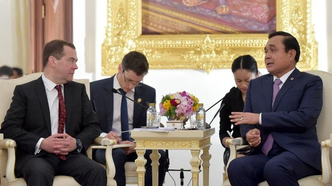 Thailand's Prime Minister Prayuth Chan-ocha (R) speaks with Russia's Prime Minister Dmitry Medvedev (L) during a news conference at the Government House