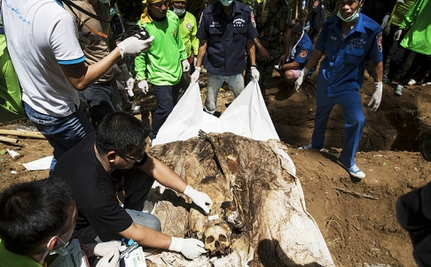 Human remains are retrieved from a mass grave at an abandoned people smuggling camp in Thailand's southern Songkhla province