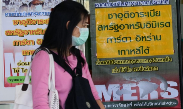 A masked woman walks past signs giving information on Mers virus in Thailand. The country confirmed its first case just as an outbreak in South Korea