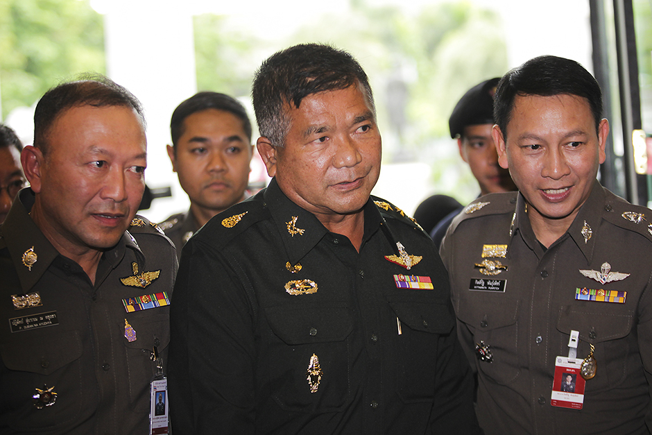 Lt-Gen Manas Kongpan (centre), a senior army adviser charged with the trafficking of Rohingya migrants, turns himself in at Royal Thai Police headquarters in Bangkok-PHOTO BY PATIPAT JANTHONG