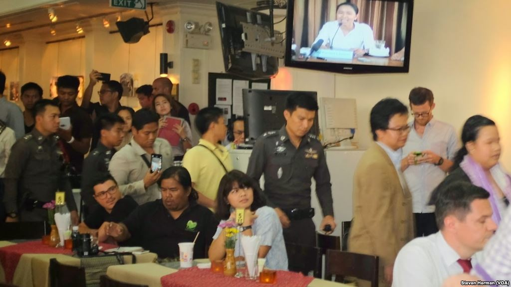 Police officers inside the Foreign Correspondents Club to deliver letters to human rights panelists