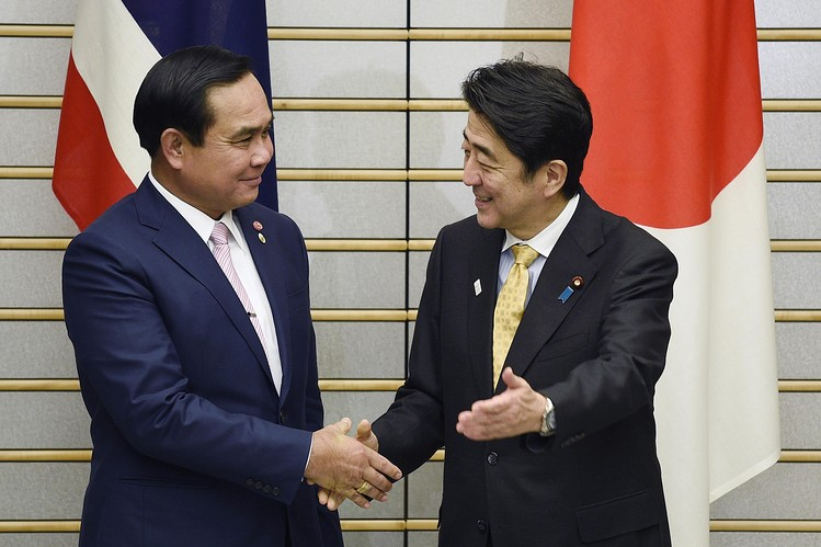 Prayuth Chan-ocha, left, and Japanese Prime Minister Shinzo Abe shake hands before their meeting at Mr. Abe's official residence in Tokyo