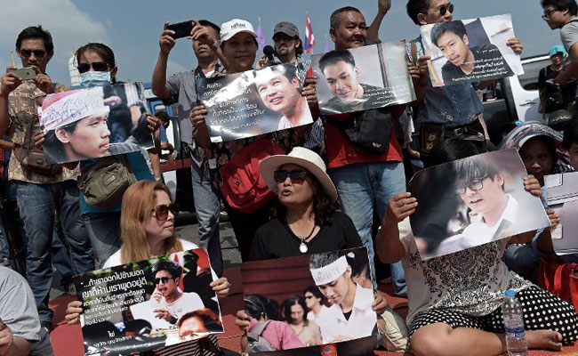 Supporters hold pictures of detained students as they take part in a protest in their support outside the cordoned-off military court where they appeared, in Bangkok