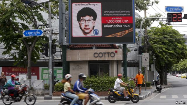 People ride their motorcycles past a digital billboard showing a sketch of the main suspect in Monday's attack on Erawan shrine, in Bangkok