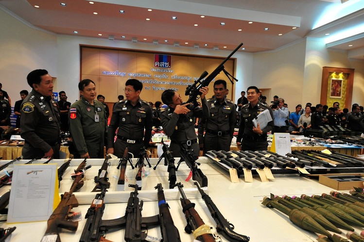 Thai police officers examine seized weapons