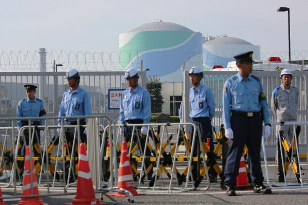 Police officers and security personnel stand in front of the gate of the Kyushu Electric Power Sendai nuclear power plant