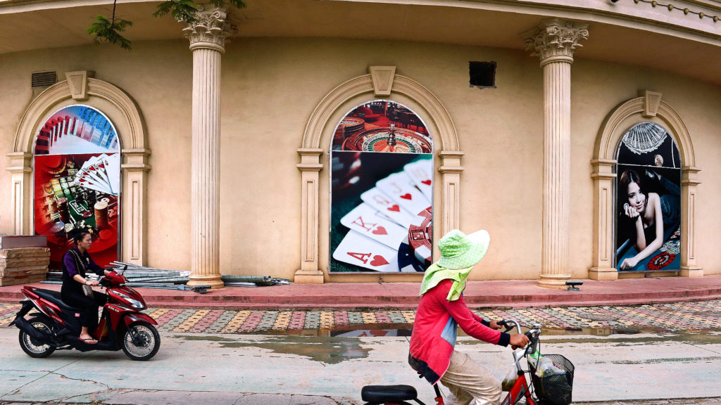 An employee rides a scooter past the Chinese-owned casino