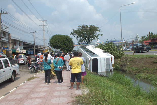 Bystanderslook at the overturned tour bus in a roadside ditch as rescue workers helptourists from Sri Lanka out of the bus. (Photo by Saichon Srinuanchan)