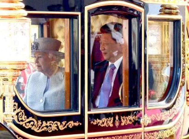 Queen Elizabeth II sits in a carriage with Chinese President Xi Jinping, right, as they travel through Horse Guards Parade, in London,