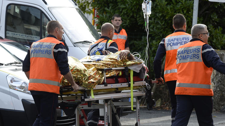Emergency crews remove an injured person from the site of a bus-truck collision in Puisseguin, France