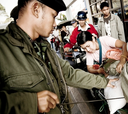 Soldier checks bags of Migrants as they enter Thailand at Mae Sai Border