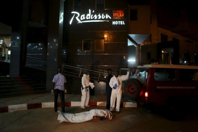 Malian officials prepare to lift a corpse into an emergency vehicle outside the Radisson hotel in Bamako, Mali.