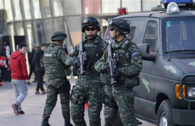 Armed policemen of the Snow Leopard Commando Unit (C) stand guard near a police van at the Sanlitun area, a fashionable location for shopping and dining, in Beijing, China, December 24, 2015. REUTERS/Jason Lee