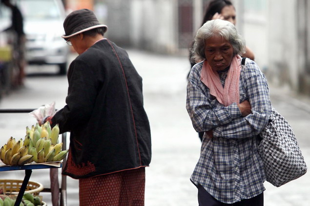Elderly woman endures the cold weather in the early morning in Chiang Rai city.