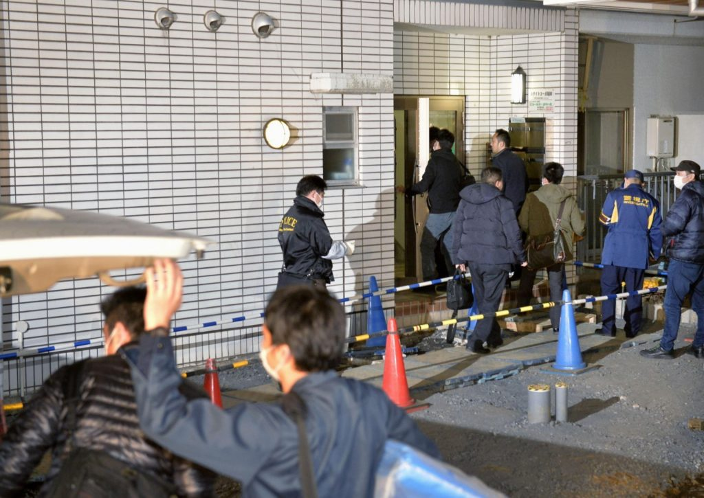 Police officers arrive for investigation of the apartment of abduction suspect Kabu Terauchi in Tokyo Monday