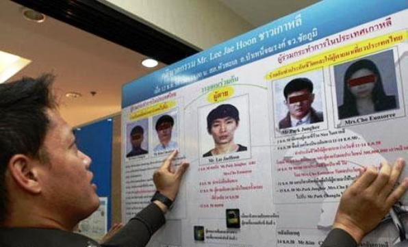A police officer prepares a chart showing the four South Korean suspects wanted for the murder of a compatriot whose body was found dumped in Chaiyaphum last December, at a media briefing on Thursday. (Photo by Apichart Jinakul)