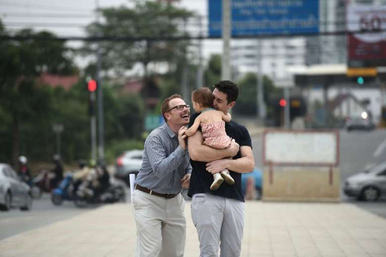 American Gordon Lake (left) and his Spanish husband Manuel Valero (right) play with their daughter Carmen in Bangkok, on March 30, 2016.PHOTO: AFP