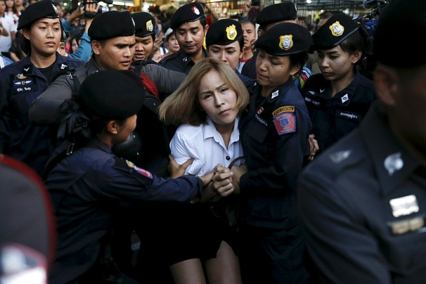 A student activist is detained during a silent protest after Thailand's election commission filed charges against a group for posting 'foul and strong' comments online criticising a military-backed draft constitution.