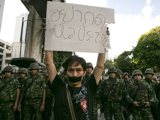 A Thai protester shows his disapproval with the military during an anti-military protest despite the law.