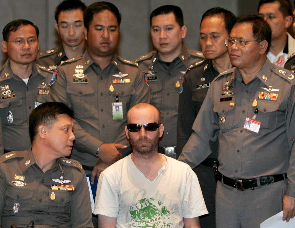 Christopher Paul Neil is surrounded by Thai policemen during a press conference at the Police Bureau