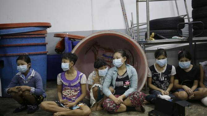 Children and teenagers sit together to be registered by officials during a raid on a shrimp shed in Samut Sakhon, Thailand. Abuse is common in Samut Sakhon, which attracts workers from some of the worldÂ's poorest countries, mostly from Myanmar. An International Labor Organization report estimated 10,000 migrant children aged 13 to 15 work in the city. Another U.N. agency study found nearly 60 percent of Burmese laborers toiling in its seafood processing industry were victims of forced labor. (AP Photo/Dita Alangkara)
