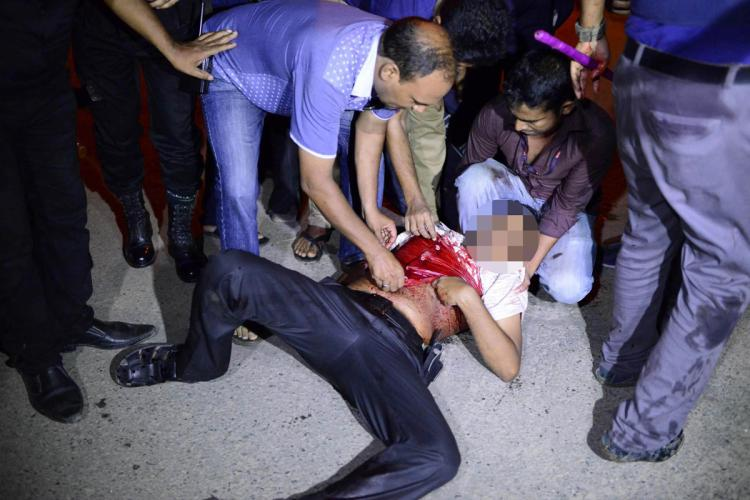 A wounded man is helped near Holey Artisan Bakery in Dhaka, Bangladesh, which was attacked by gunmen Friday night. (Mahmud Hossain Opu/Getty Images)