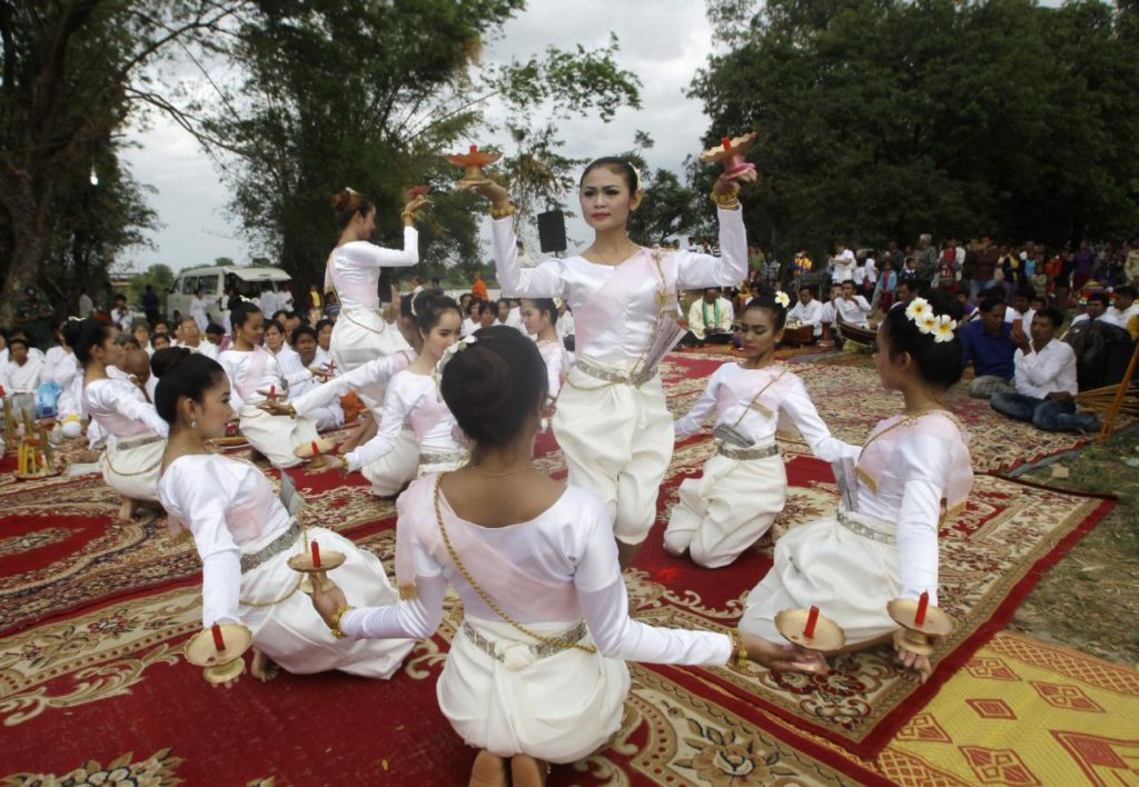 Cambodian dancers perform during a Buddhist ceremony to pray before they search for missing Buddha statues in the Tonle Sap river