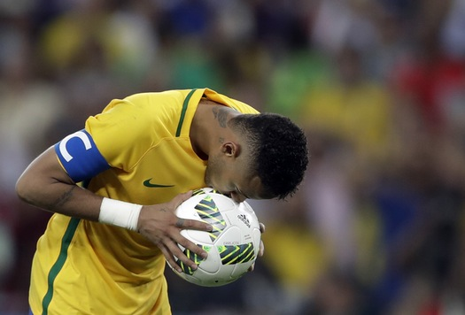Brazil's Neymar kisses the ball before scoring the decisive penalty kick during the final match of the mens's Olympic football tournament.
