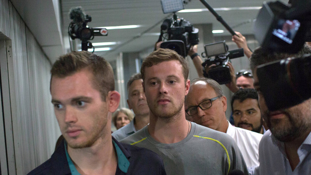 Journalists surround American Olympic swimmers Gunnar Bentz, left, and Jack Conger, center, as they leave the police station at Rio International airport early Thursday Aug. 18, 2016.