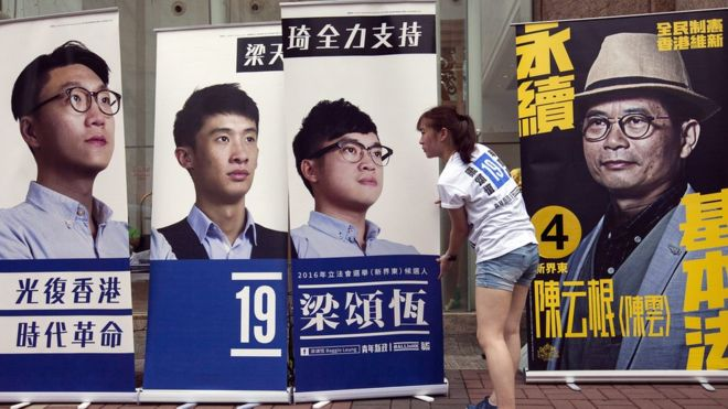 A woman adjusts one of four larger-than-life posters for candidates in Hong Kong