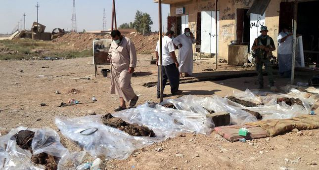 Iraqis inspect the bodies found in a mass grave and displayed for identification in the nearby town of Tuz Khurmatu, northeast of Baghdad, Iraq
